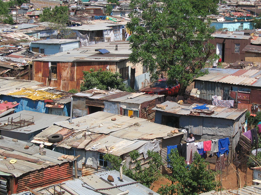 What are the four contributory factors to poor living conditions locally and globally?